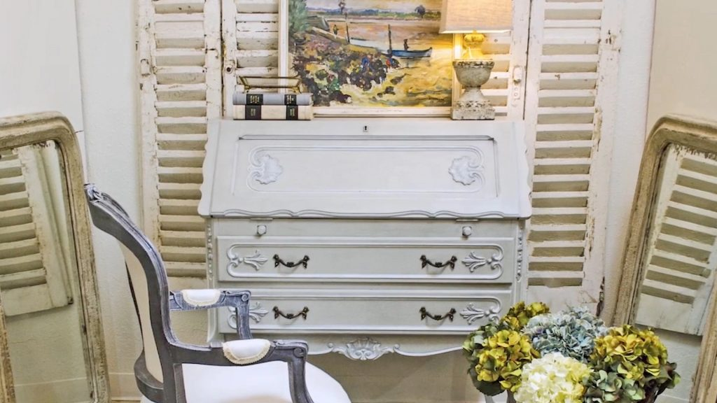 Amitha Verma Chalk Finish Paint makeover antique secretary paired with antique chair painted in Chambord Gray against a wall of shutters.