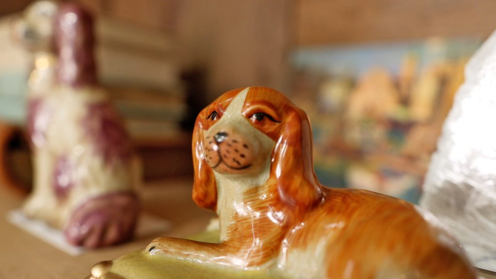 One orange Staffordshire ceramic dog laying down on a bookshelf in orange colorway, a resurging farmhouse design trend for 2021, by Amitha Verma.