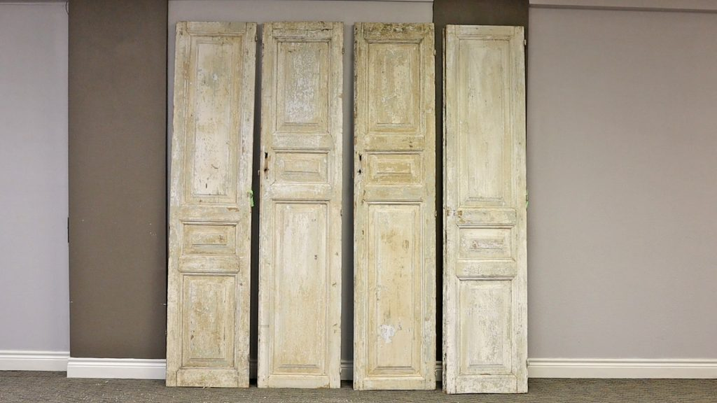 Four large distressed wooden door panels to be used in Amitha Verma's closet in her office makeover.