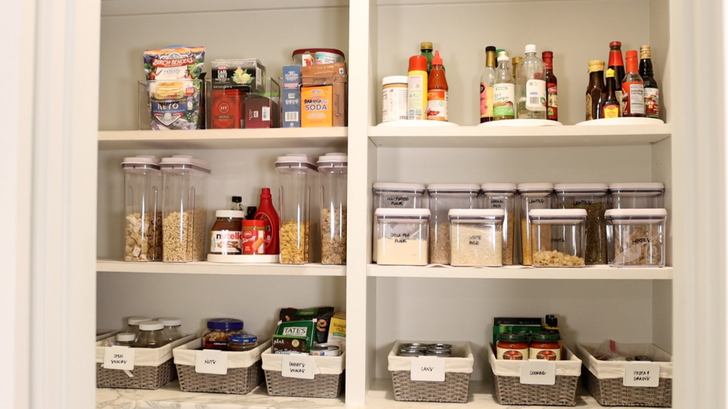 A display of clear containers topped up with dried foods and gray wicker baskets filled with cans, sauces, nuts, and snacks reveals Amitha Verma's finished farmhouse pantry organizing project.