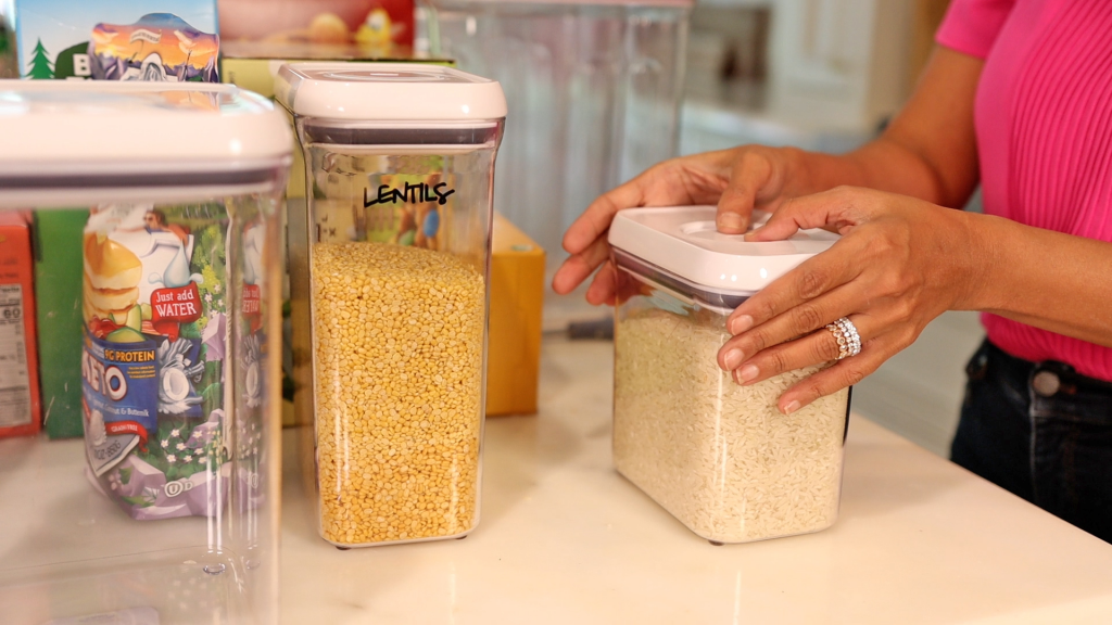 Amitha Verma transfers rice and lentils into labeled clear containers as part of her farmhouse pantry organizing system.