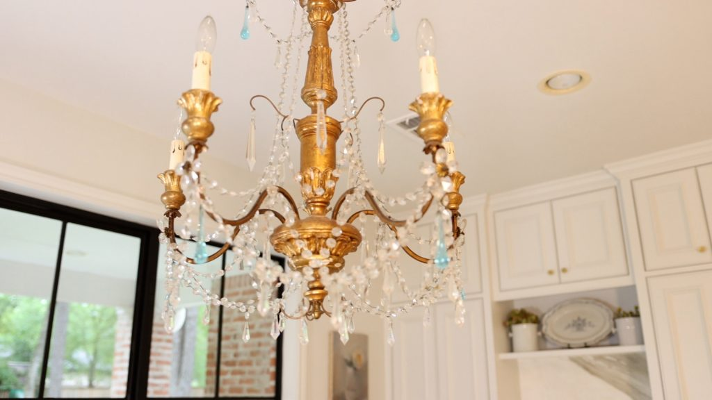 A glam chandelier hangs from Amitha Verma's kitchen ceiling with gold painted wood and glass crystals.
